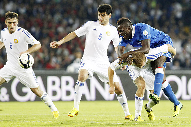 Armenia's Karlen Mkrtchyan (left), Robert Arzumanyan (2nd from left) and Varazdat Haroyan (right) challenge Italy's Mario Balotelli during their 2014 World Cup qualifying match at San Paolo stadium in Naples on TUesday