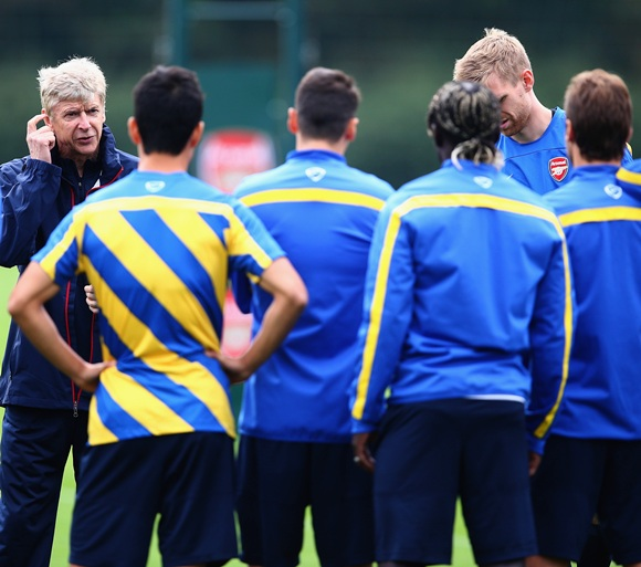 Manager Arsene Wenger of Arsenal talks to his players during a training session