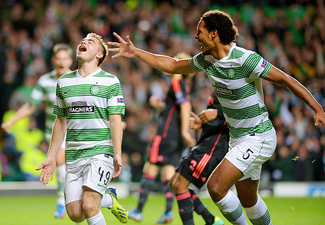 James Forrest (left) of Celtic is congratulated by teammate Virgil van Dijk after scoring the opening goal from the penalty spot during their UEFA Champions League Group H match against Ajax at Celtic Park Stadiumin Glasgow, Scotland, on Tuesday
