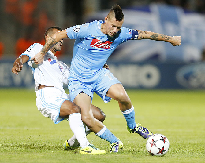 Olympique Marseille's Alexis Romao (left) challenges Napoli's Marek Hamsik during their Champions League match at the Velodrome stadium in Marseille on Tuesday