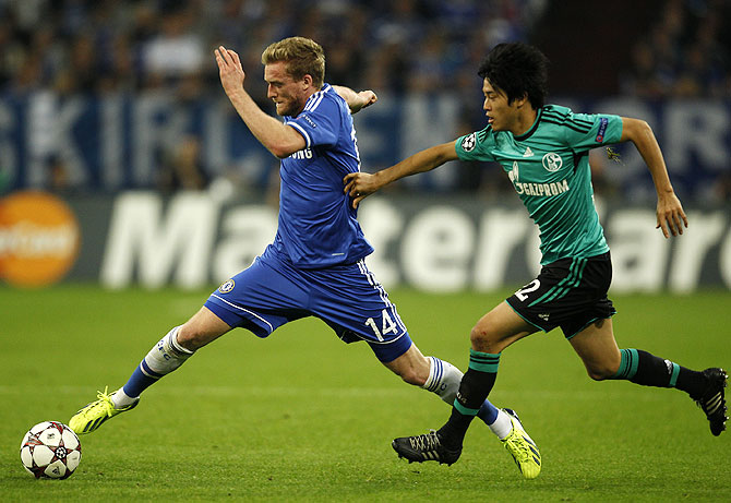 Chelsea's Andre Schuerrle (left) is challenged by Schalke 04's Atsuto Uchida during their Champions League match in Gelsenkirchen, Germany on Tuesday