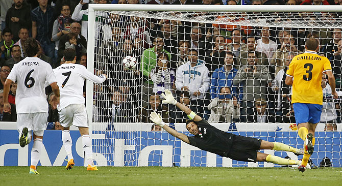 Real Madrid's Cristiano Ronaldo (2nd from left) scores a penalty past Juventus's goalkeeper Gianluigi Buffon during their Champions League match at Santiago Bernabeu on Wdnesday
