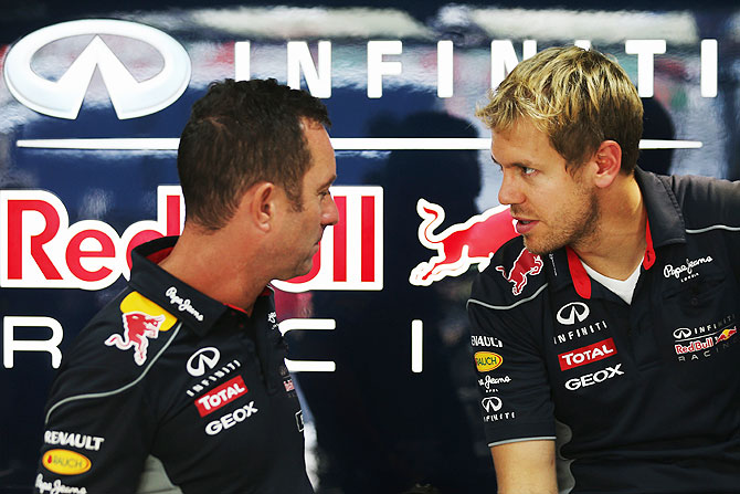 Sebastian Vettel of Germany Red Bull Racing talks with Chief Mechanic Kenny Handkammer in their team garage during previews for the Indian Formula One Grand Prix at Buddh International Circuit on Thursday
