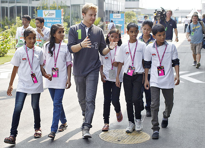 Mercedes Formula One driver Nico Rosberg (centre) of Germany walks with Indian school children in the paddock at the Buddh International Circuit in Greater Noida on Thursday