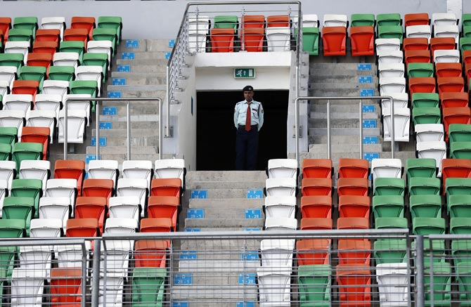 A security guard stands amid empty seats on the grandstand at the Buddh International Circuit in Noida