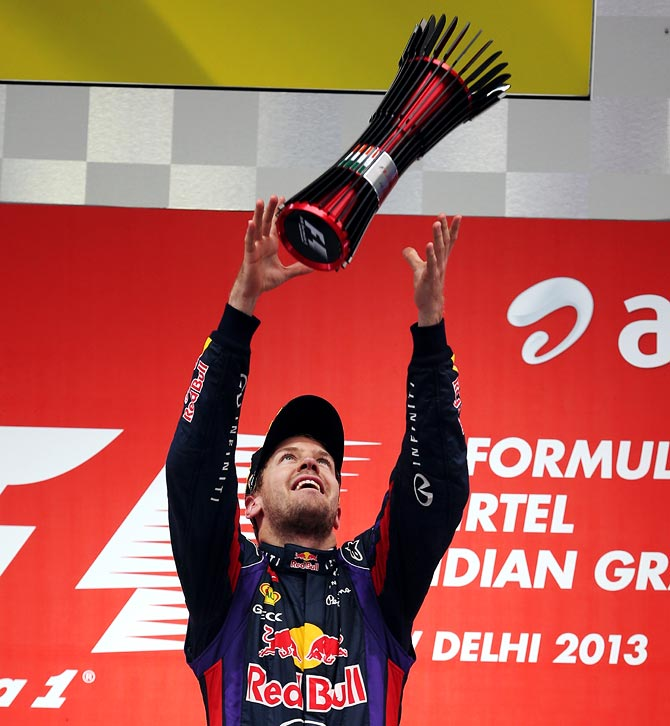 Sebastian Vettel throws his trophy in the air on the podium after winning the Indian F1 Grand Prix
