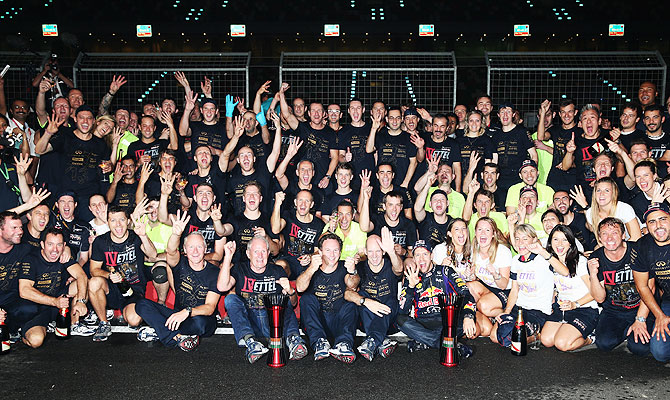 Race winner and 2013 Formula One World Champion Sebastian Vettel of Germany and Infiniti Red Bull Racing celebrates with teammates following the Indian Formula One Grand Prix at Buddh International Circuit in Noida on Sunday