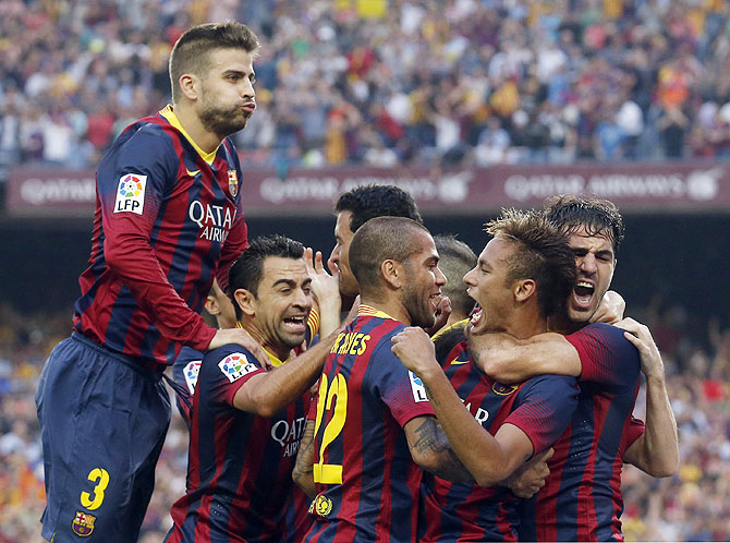 Barcelona's Neymar (2nd from right) is congratulated by teammates (left to right) Gerard Pique, Xavi, Dani Alves and Cesc Fabregas after scoring a goal against Real Madrid during their La Liga Clasico match at Nou Camp stadium in Barcelona on Saturday