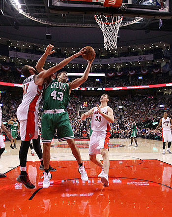 Kris Humphries #43 of the Boston Celtics battles for a rebound with Jonas Valanciunas #17 of the Toronto Raptors as Tyler Hansbrough #50 of the Toronto Raptors looks on