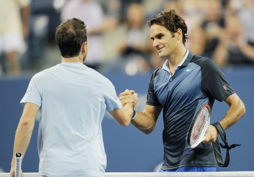 Roger Federer of Switzerland is congratulated by Adrian Mannarino of France