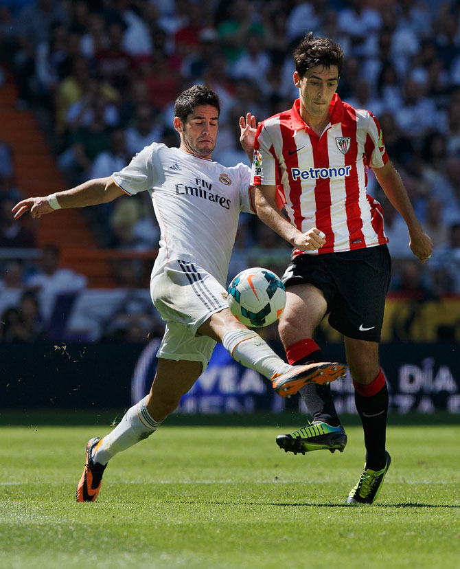 Real Madrid's Isco (left) and Athletic Bilbao's Andoni Iraola (right) vie for possession during their La Liga match at Estadio Santiago Bernabeu in Madrid on Saturday