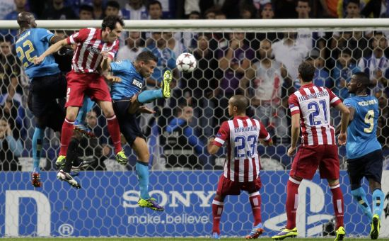Atletico Madrid's Diego Godin (2ndL) heads the ball past Porto's players to score a goal during their Champions League soccer match at Dragao stadium
