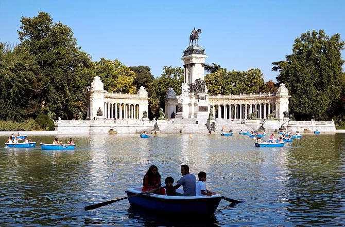 People on rowboats at the Retiro Park pond with Alfonso the Twelfth of Spain monument in the background in Madrid