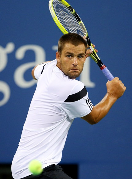 Mikhail Youzhny of Russia returns a backhand