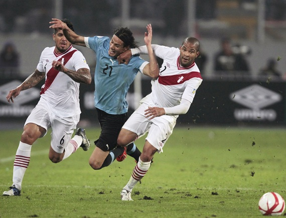 Uruguay's Edinson Cavani (centre) is challenged by Peru's Alberto Junior Rodriguez (right) and Juan Manuel Vargas