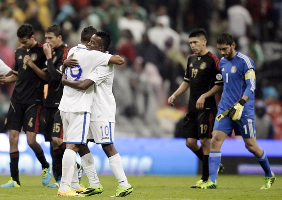 Luis Fernando Garrido (19) and Marvin Chavez (10) of Honduras celebrate their team's victory as players of Mexico react