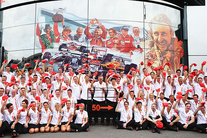 Jenson Button, Martin Whitmarsh and Sergio Perez and McLaren teammates pose for a team photograph as they celebrate their 50th year in Formula One during the Italian Formula One Grand Prix on Sunday