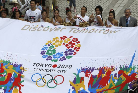 Participants hold a banner during an event celebrating Tokyo being chosen to host the 2020 Olympic Games