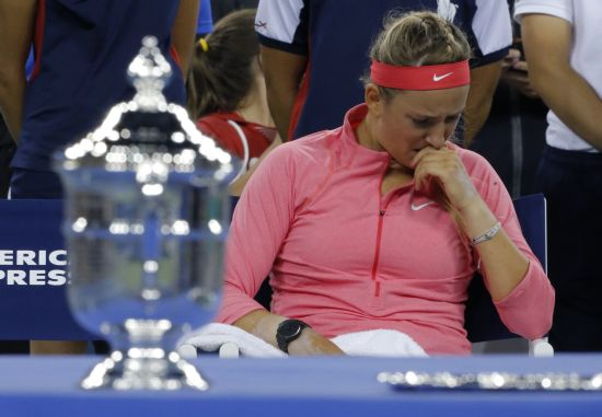 Victoria Azarenka of Belarus wipes her face as she sits by the winner's trophy