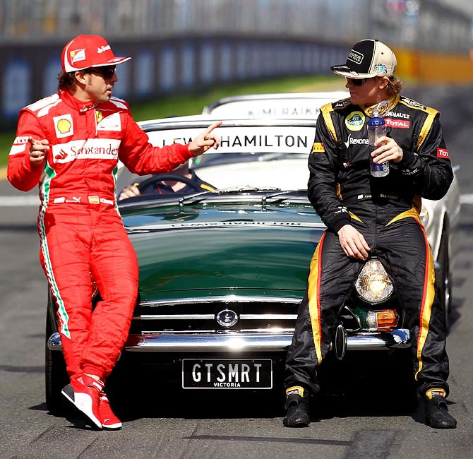 Fernando Alonso (left) speaks to Kimi Raikkonen
