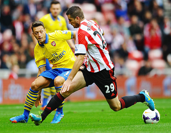Mesut Oezil of Arsenal challenges Valentin Roberge of Sunderland during their English Premier League match at the Stadium of Light in Sunderland on Saturday