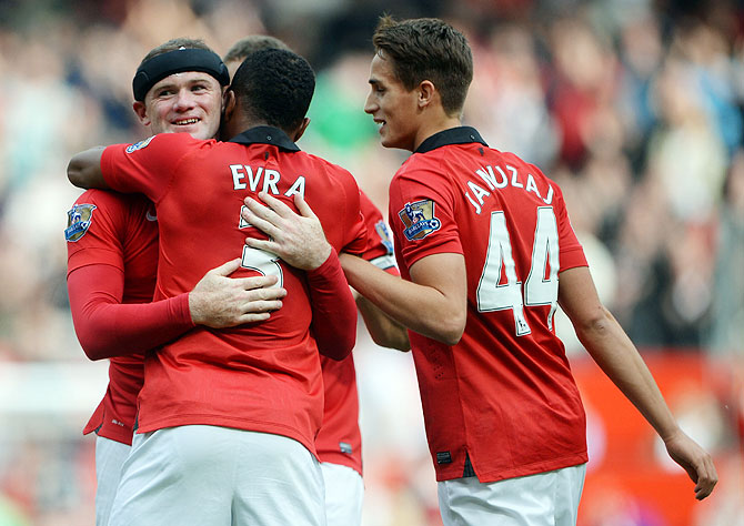 Wayne Rooney of Manchester United is congratulated by Patrice Evra (3) and Adnan Januzaj (44) after scoring against Crystal Palace at Old Trafford in Manchester on Saturday