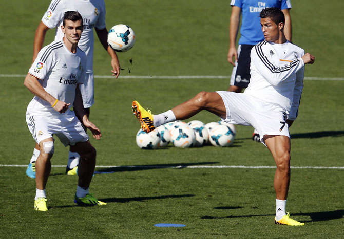 Real Madrid's Gareth Bale (L) and Cristiano Ronaldo challenge for the ball during their training session at Valdebebas sports grounds in Madrid