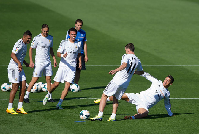 Real Madrid's new signing Gareth Bale is tackled by Cristiano Ronaldo while team mates Jese Rodriguez (left), Karim Benzema (second left), Pepe and assistant coach Zinedine Zidane look on