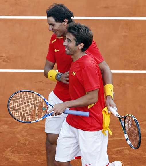Spain's Rafael Nadal (top) celebrates with teammate Marc Lopez