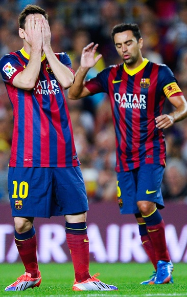 Lionel Messi (left) and Xavi of FC Barcelona reacts after missing a chance to score