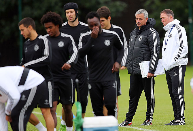 Jose Mourinho and his support team watch as Chelsea players prepare for a training session at the Cobham traning centre on Tuesday