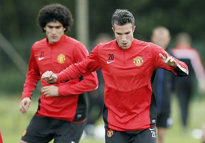 Manchester United's Robin van Persie (right) and Marouane Fellaini warm up during a training session