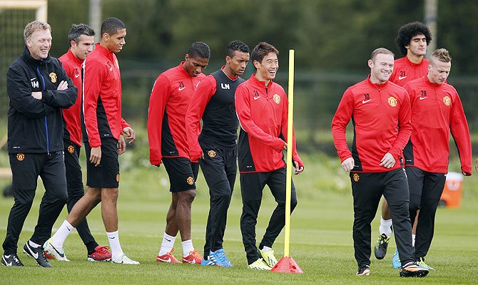 Manchester United's manager David Moyes (left) shares a laugh with teammates during a training session