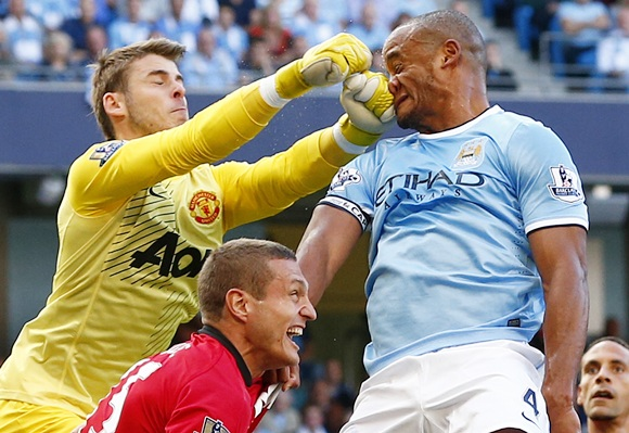 Manchester City's Vincent Kompany (right) gets hit in his face as he is challenged by Manchester United's David de Gea