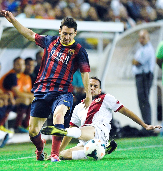 Lionel Messi of FC Barcelona duels for the ball with Nacho Martinez of Rayo Vallecano