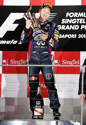 Sebastian Vettel of Germany and Infiniti Red Bull racing lifts the trophy following his victory during the Singapore Formula One Grand Prix