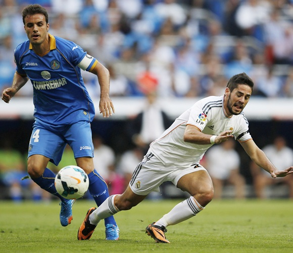 Real Madrid's Isco is tackled by Getafe's Pedro Leon