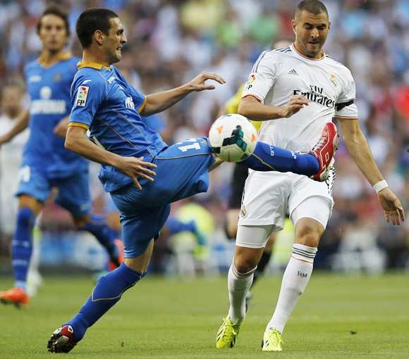 Real Madrid's Karim Benzema (right) and Getafe's Alvaro Arroyo fight for the ball