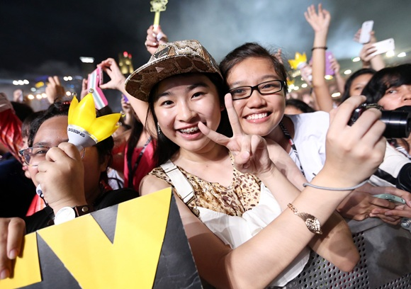Fans of Korean Pop Band Bigbang watch as they perform at the Singapore Formula 1 Grand Prix