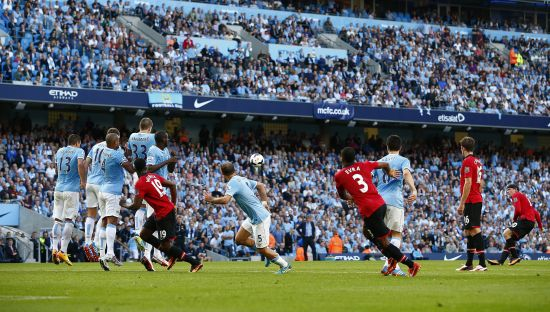 Manchester United's Wayne Rooney (R) shoots to score against Manchester City