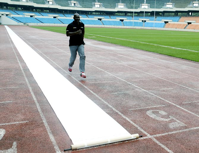 Ben Johnson of Canada runs next to a scroll petition laid out on the track at the Seoul Olympic Stadium