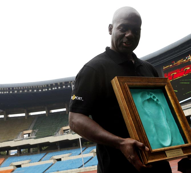 Ben Johnson holds a cast of his footprint made after running on the track at the Seoul Olympic Stadium