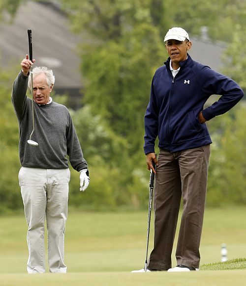 Senator Bob Corker (R-TN) lines up his putt as he plays golf with Obama