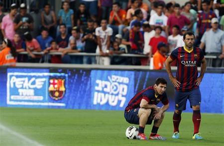 Barcelona's Lionel Messi (left) sits on a ball next to teammate Javier Mascherano