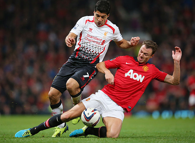 Jonny Evans of Manchester United tackles Luis Suarez of Liverpool during their League Cup match at Old Trafford on Wednesday