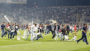 Besiktas fans throw plastic chairs onto the pitch during the Turkish Super League derby soccer match between Besiktas and Galatasaray at Ataturk Olympic Stadium in Istanbul on Sunday