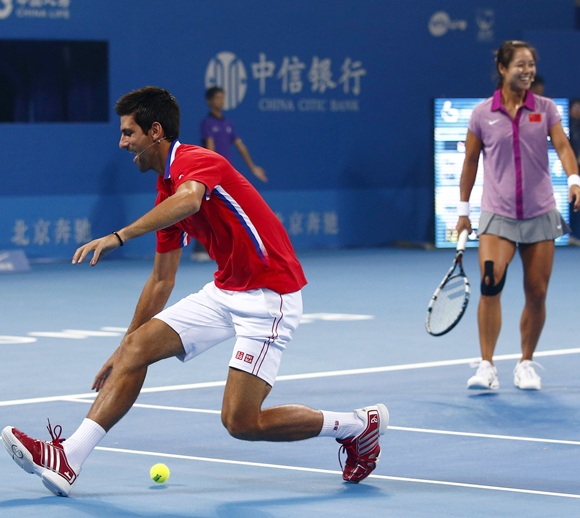 Serbia's Novak Djokovic (left) tries to catch the ball as China's Li Na looks on