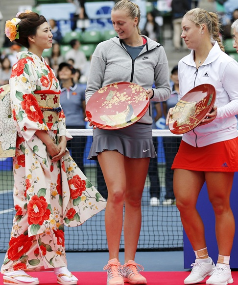 Petra Kvitova (centre) of the Czech Republic and Angelique Kerber (right) of Germany hold their trophies as they look at a woman dressed in a kimono