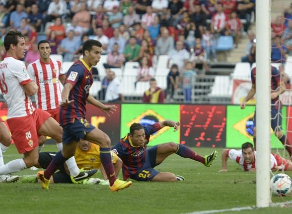 Barcelona's Adriano Correia (centre) scores past Almeria's Esteban Andres Suarez