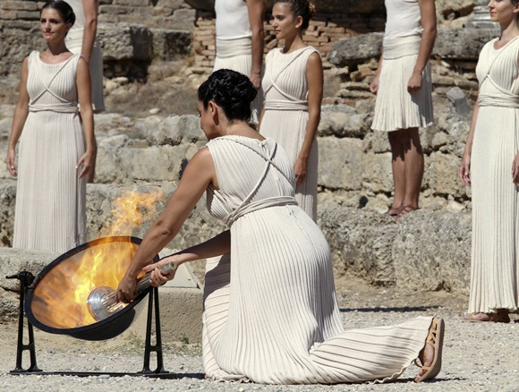 Greek actress Ino Menegaki (front), playing the role of High Priestess, lights a torch from the sun's rays reflected in a   parabolic mirror during a dress rehearsal for the torch lighting ceremony of the Sochi 2014 Winter Olympic Games